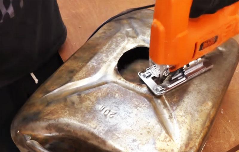 Электрическим лобзиком вырезается очерченная окружность в обоих бортах канистры