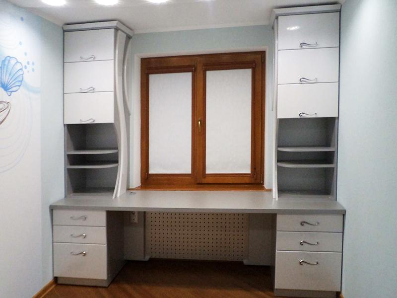 Прямой стол на всю стену – лучший вариант. По бокам устанавливаются полки и ящики для хранения личных вещей
