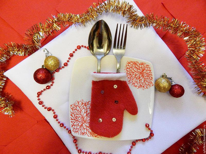 Выберите небольшие варежки или носки для подарков и сложите в них столовые приборы. Так вы усилите дух праздника и удивите гостей, привыкших к обычным тканевым салфеткам
