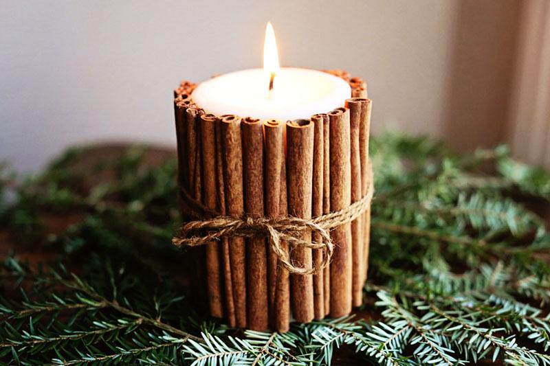 Выбирайте большие и толстые белые свечи без запаха. При горении они будут отдавать тепло, отчего дом наполнится мягким и тёплым ароматом корицы. Чтобы дополнить композицию, положите свечу на ветку ели