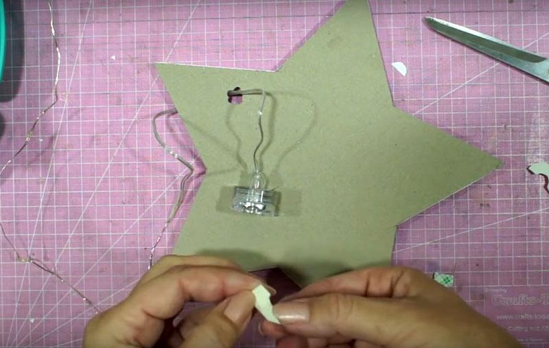 Проденьте нитку гирлянды сквозь приготовленное отверстие, а корпус управления закрепите двухсторонним скотчем на задней стороне лампы