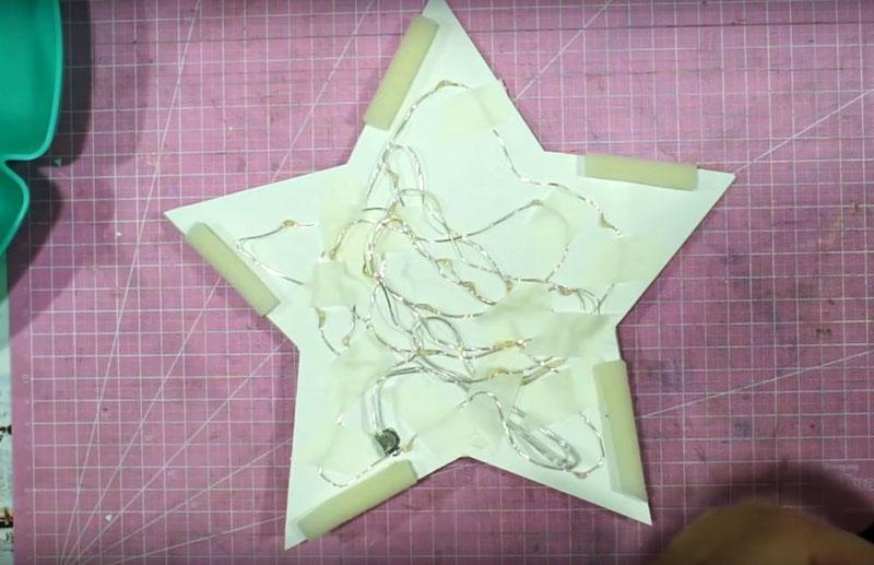 Наклейте первую бумажную деталь на картон и прикрепите к ней гирлянду малярным скотчем, располагая его между лампочками
