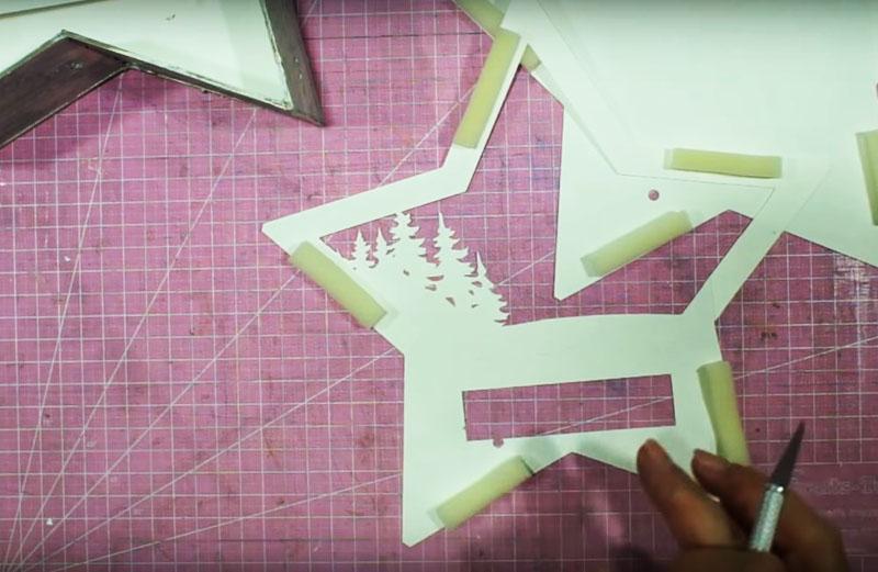 В нижней части бумажных шаблонов сделайте такие небольшие отверстия для подсветки картинки снизу. Следите за тем, чтобы эти отверстия не были заметны с передней стороны картинки