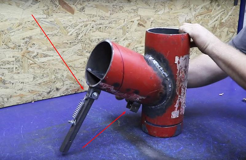 Автор сделал основной упор таким образом: кусок трубы на наклонной части печки фиксируется с одной стороны на корпусе, а вторым втыкается в землю или упирается в неё. Для удобства переноски упор можно убирать и закреплять его на корпусе
