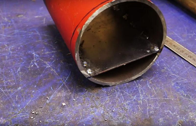 В наклонной трубе вварена плоская площадка. Она направит дрова в нужном направлении к топке
