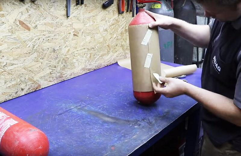Для начала нужно обрезать их с двух сторон, чтобы превратить изделия в кусок трубы. Чтобы ровно отметить линию распила, используйте лист бумаги. Просто оберните огнетушитель им и по краю сделайте отметку