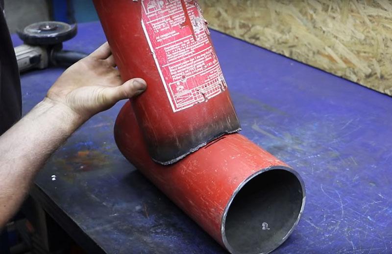 Приложите обрезанную трубу ко второй детали и снова обрисуйте контур. Следующее отверстие нужно вырезать также резаком или по упрощённой схеме с использованием дрели