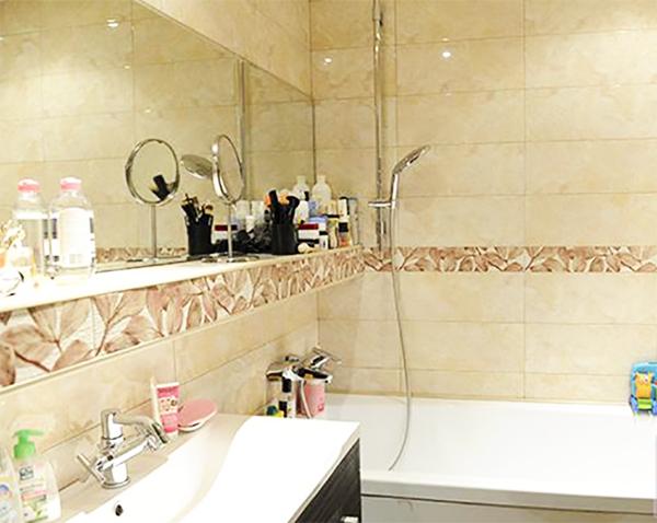 Монохромная плитка в ванной комнате дополнена бордюром с цветочным принтом