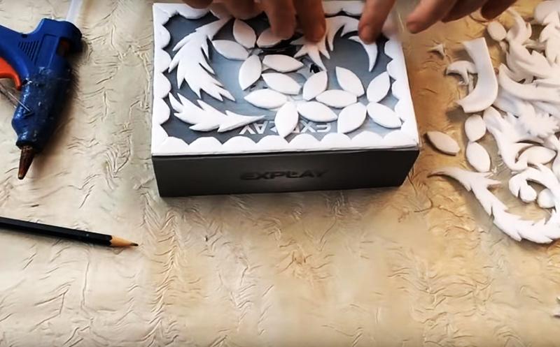 Сформируйте из пенопластовых деталей рисунок, форму которого вам подскажет фантазия. Обклейте не только крышку коробки, но и боковые стороны