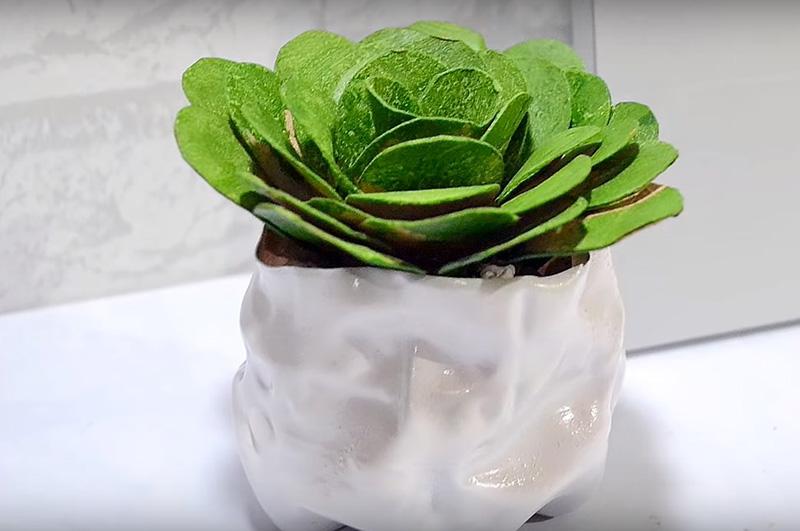 Горшочек для искусственного цветка можно сделать из обычной пластиковой бутылки. Обрежьте её и деформируйте горячим феном. Покрасьте горшочек краской, а внутрь насыпьте небольшие камни. Остаётся только вставить ваш цветочек в горшок и украсить им рабочий стол