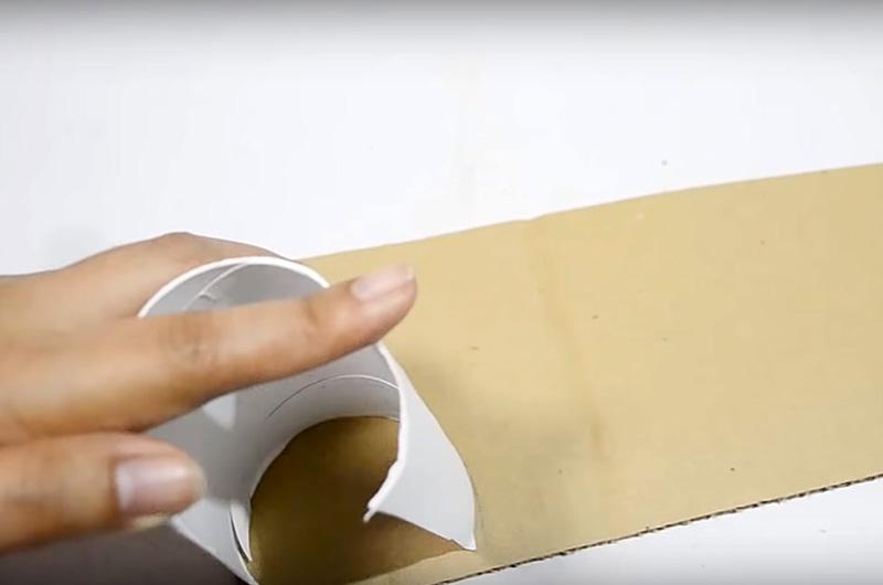 Разрежьте тубу вдоль и слегка разверните, но не полностью. Приложите заготовку к листу картона и обрисуйте форму для 4 заглушек