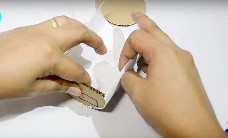Закрепите картонные заглушки в тубе с помощью горячего клея