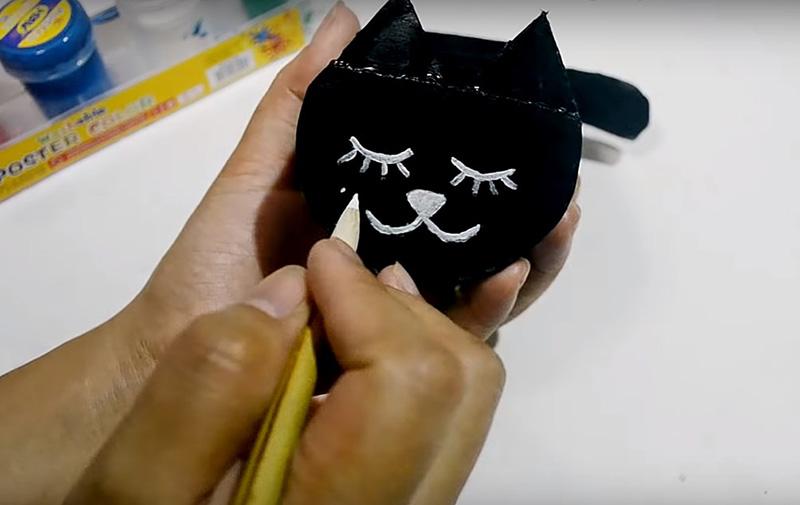 На той части, где вы приклеили ушки, нарисуйте контрастной краской забавную мордочку