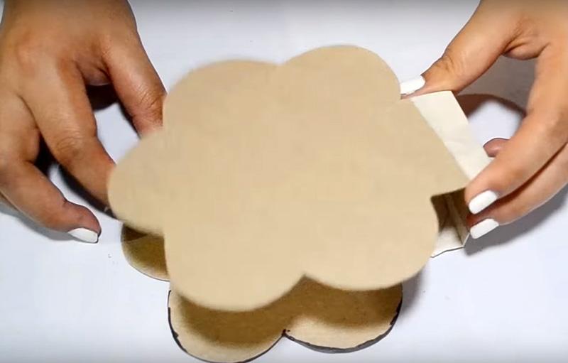 Приготовьте такую деталь, которая будет одновременно дном и крышкой будущей шкатулки. Для этого обведите на картоне заготовку из туб и соедините части малярным скотчем. Затем эту основу обклейте тканью или декоративной бумагой
