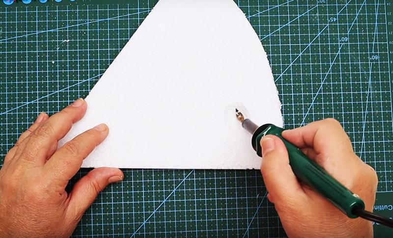 Вырежьте из пенопласта треугольник. Для сырных дырочек потребуется сделать круглые углубления. Они отлично получаются, если использовать паяльник. Слегка надавливая, прижмите его к поверхности пенопласта. Он оплавится. Запах будет не очень, так что лучше открыть окно