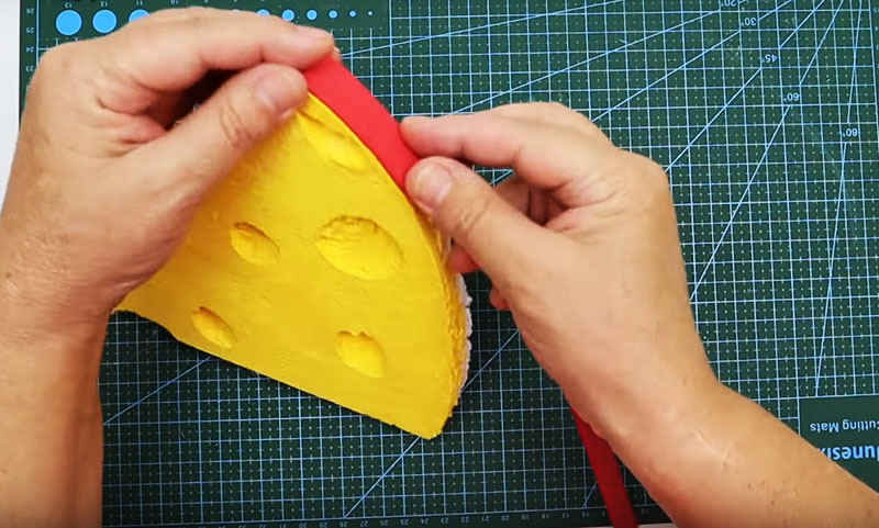 На округлую сторону вашего сырного кусочка наклейте полосу красной ленты, фоамирана или хотя бы красного скотча. Получится очень натуралистично