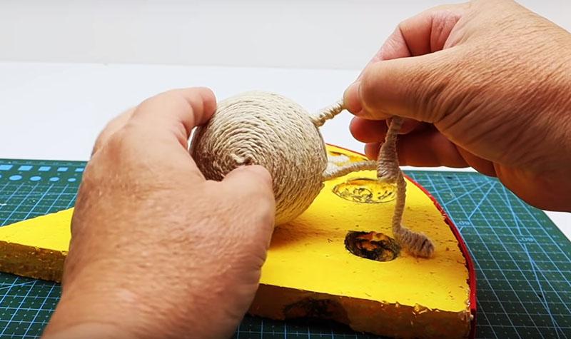 Зафиксируйте шарик туловища на сырной подставке так, чтобы прорезь для монет находилась строго вверху. Потом вставьте ножки и согните их в нужное положение, а место их соприкосновения с шариком и подставкой дополнительно закрепите клеем