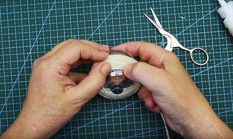 Нанесите клей на поверхность шарика и последовательно начните обматывать его, оставляя прорезь для монет открытой. В некоторых местах, например над прорезью, шнур придётся обрезать. Подклейте его края, чтобы нитки не торчали