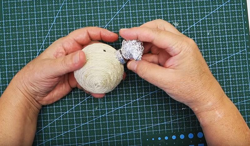 Из куска пищевой фольги сформируйте голову мышонка с длинным носом. Она будет располагаться там, где у ёлочного шарика находится крепление