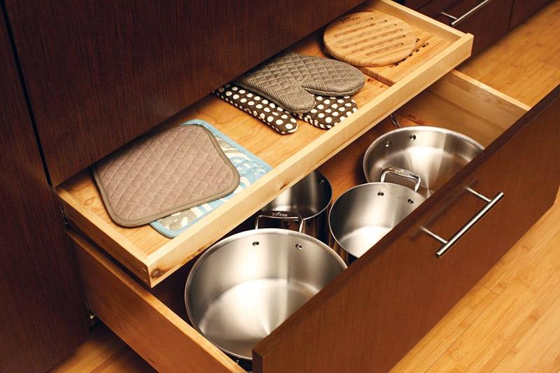Крупные кастрюли, тяжёлую кухонную технику и разделочные доски убирайте в нижние ящики