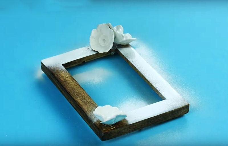 После декорирования, всю рамку следует покрыть краской из распылителя. Автор использовал белую акриловую, но также неплохо будет выглядеть и оттенок, имитирующий металлический блеск
