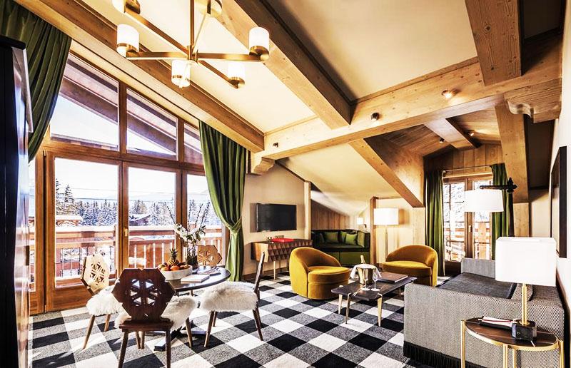 Сочетание горчичного цвета в мебели и зелёных занавесок смотрится выигрышно. При этом номер выглядит необычно за счёт покатой крыши и больших окон на всю стену. Интересная деталь – резные спинки стульев
