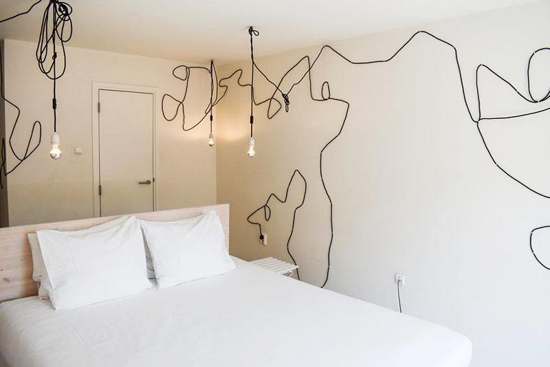 Один из номеров Hotel The Exchange выполнен в стиле «минимализм». Главная «фишка» декора – белые стены и рисунок из проводов, а также свисающие с потолка лампочки