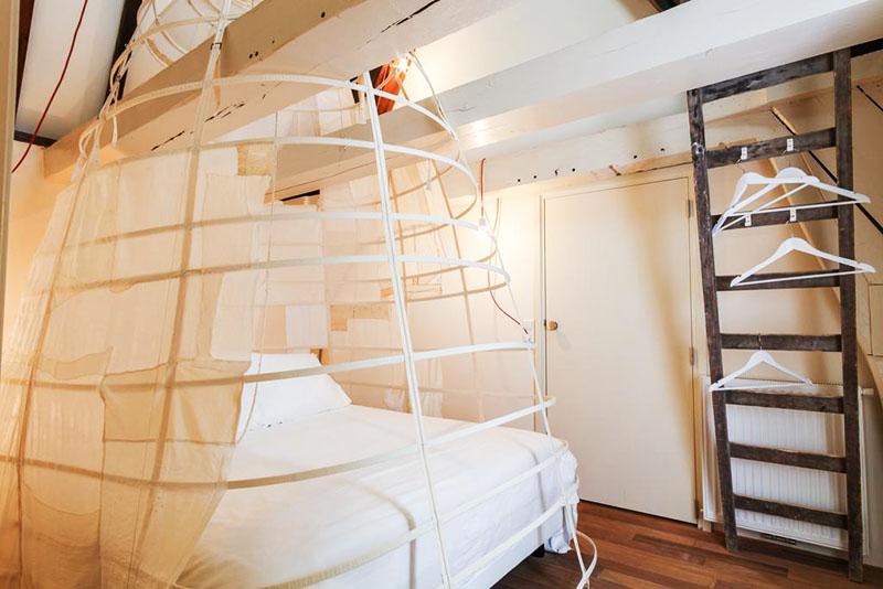 Необычный вариант оформления спальни – кокон вокруг кровати и шкаф-лестница, на которой гости хранят одежду