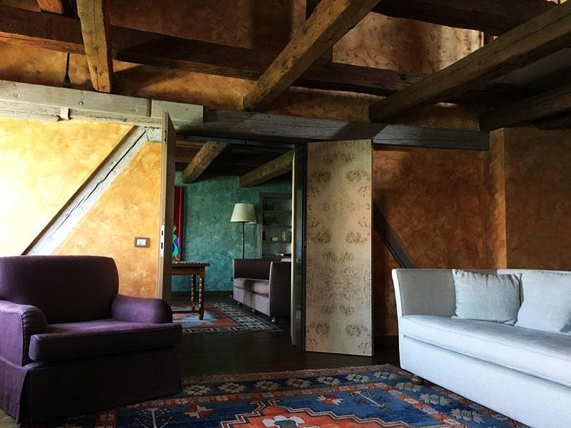 На фоне старинного интерьера и деревянных балок красиво смотрятся современные диваны