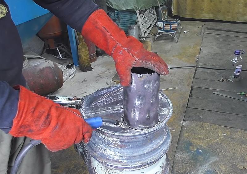 В отверстие вваривается кусок трубы, а уже к нему подсоединяется металлическая гофра, которая выводится за пределы помещения