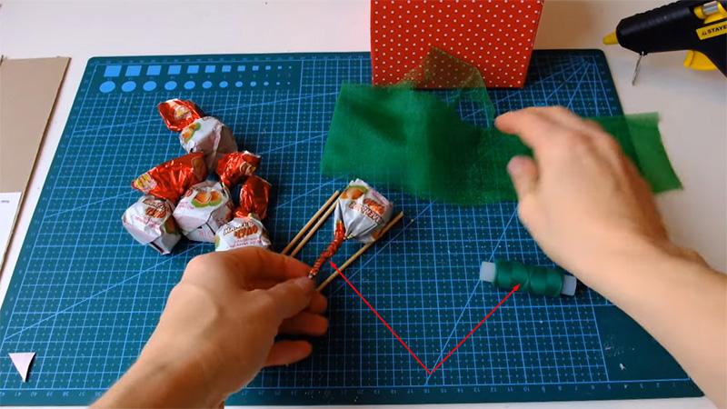 Конфеты фиксируются на шпажках при помощи зелёной нитки