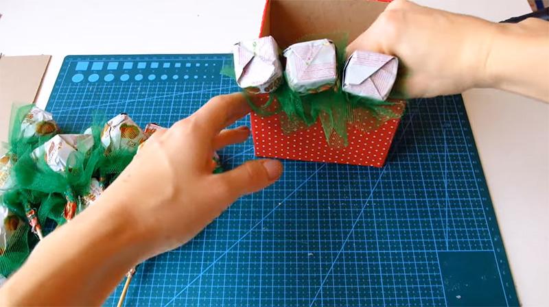 Начиная от краёв, конфеты на шпажках размещаются в коробочке