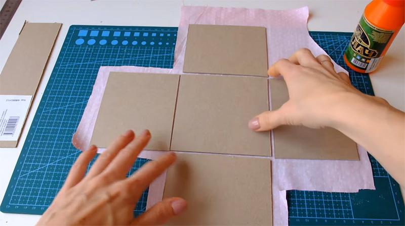 Нарезанный картон требуется правильно разложить на ткани перед началом сборки коробки