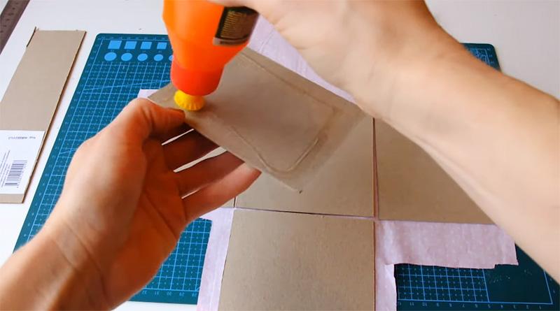 Картон промазывается клеем и прижимается к ткани