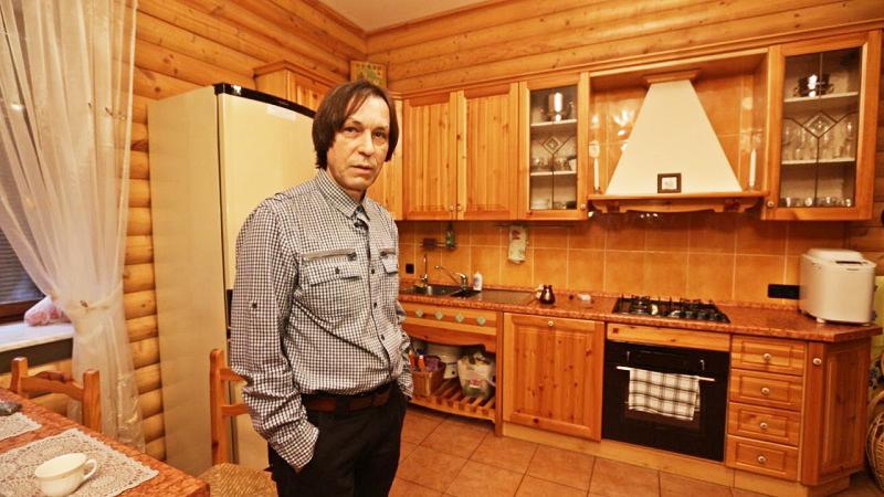 Стены кухни полностью обшиты деревом, а для пола выбрали более практичный кафель