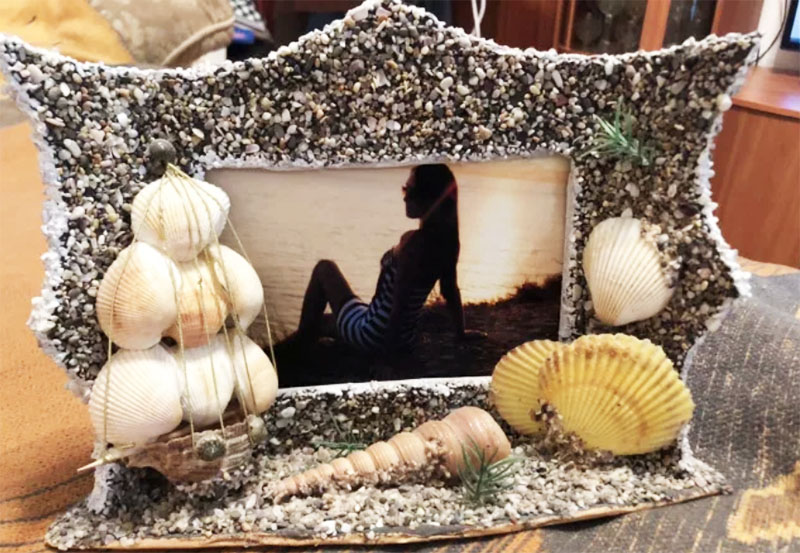 Рамку покрыть клеем, сверху присыпать промытым песком и декорировать ракушками