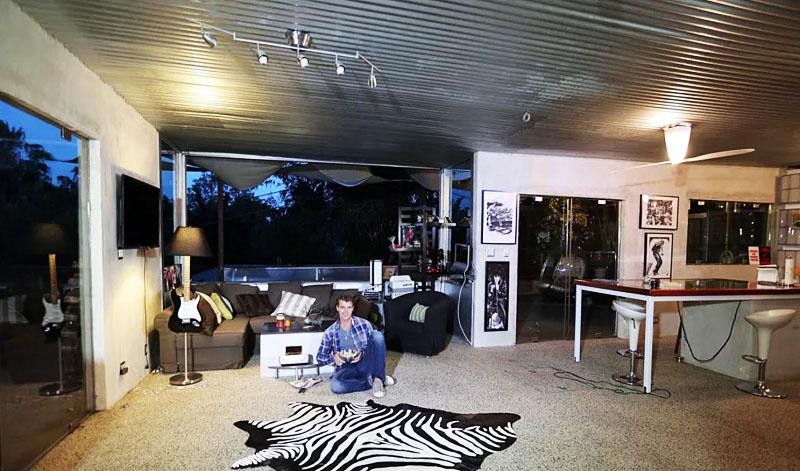 В зоне отдыха поставили угловой диван и кресло с большим количеством контрастных декоративных подушек