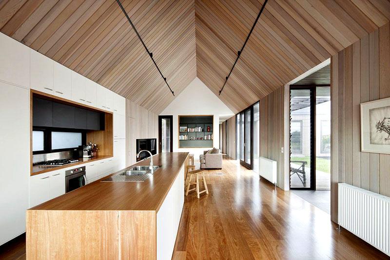 Потолок под двускатной крышей будет смотреться стильно и необычно, если использовать для отделки доски