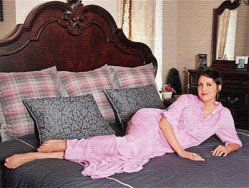 Огромную двуспальную кровать, изготовленную из натурального дерева, украшает высокое фигурное изголовье