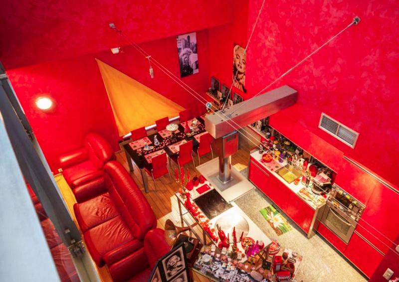 Обеденная зона и кухня отделены от гостиной роскошными красными диванами
