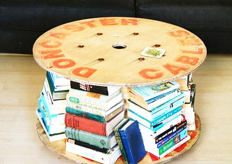 Необычная бюджетная идея – изготовление стола из большой катушки. Это хороший вариант, если вы не хотите портить книги. Просто разложите их по кругу
