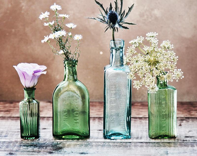 Не старайтесь найти идеально белую бутылку и вычистить её до блеска – лучше всего подойдут зелёные, коричневые и голубые ёмкости. Если вам покажется, что ваза выглядит скучно, используйте для декора широкую атласную или джутовую ленту