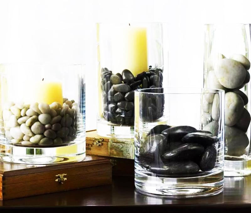 Используйте не только мелкую гальку, но и крупные чёрные камни. Для дополнительной гладкости можете покрыть их обычным бесцветным лаком. Сверху можете поставить большие белые свечи или сухоцветы