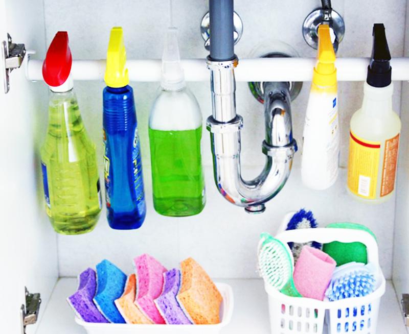 Приобретите пластиковую или металлическую перекладину для занавесок в ванной, и прикрепите её к стенкам шкафа. На такой палке хорошо крепятся бытовые средства с разбрызгивателями, а внизу остаётся больше места для негабаритных предметов