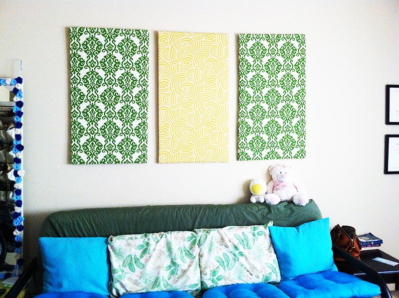 Разместите по центру стены одно панно ярко-жёлтого, зелёного или синего цвета, а по бокам от него повесьте панно того же размера, но с другим оттенком ткани