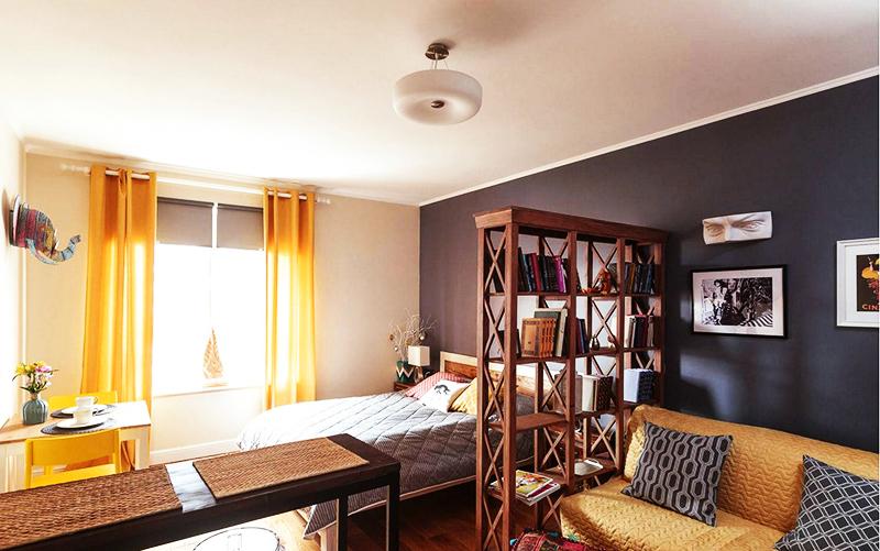 Самый простой вариант зонирования – разделение спальни на несколько зон с помощью стеллажа и дивана или длинного стола