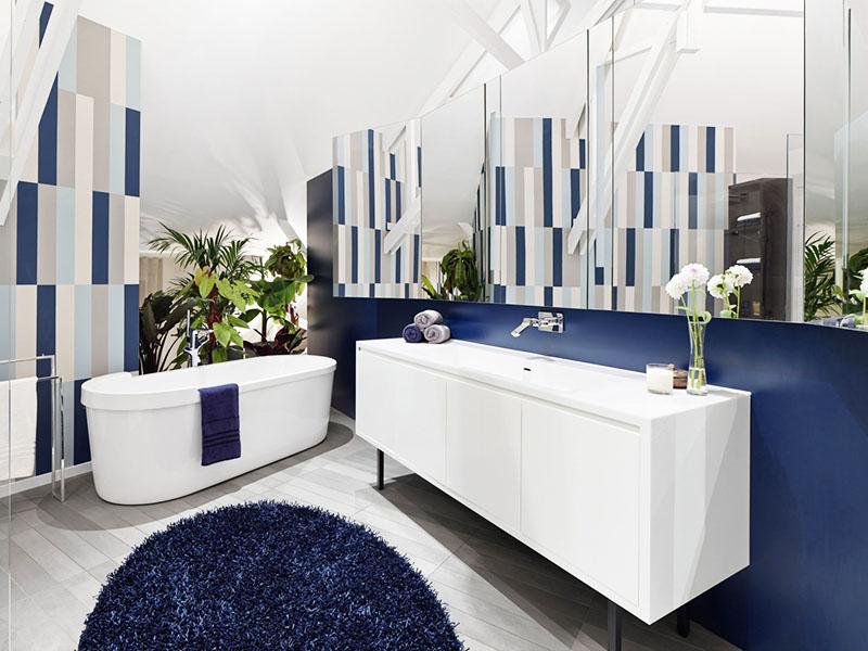 Стильное и необычное оформление стены в ванной – сочетание серого, голубого, белого и синего цвета. Используйте для отделки плитку, обои или просто покрасьте стену краской
