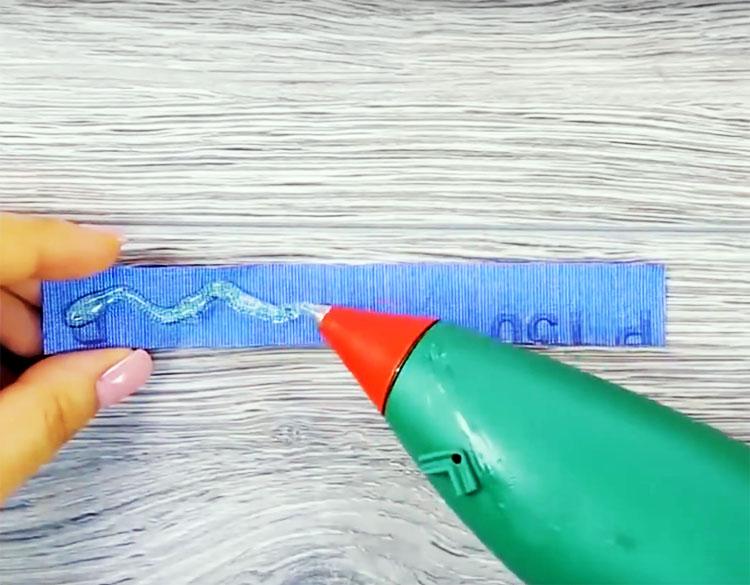 Отрежьте полоску наждачной бумаги и нанесите на нее термоклей