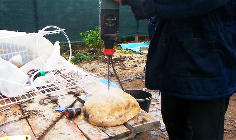 В речном камне требуется пробурить отверстие диаметром 10 мм и вставить в него шланг