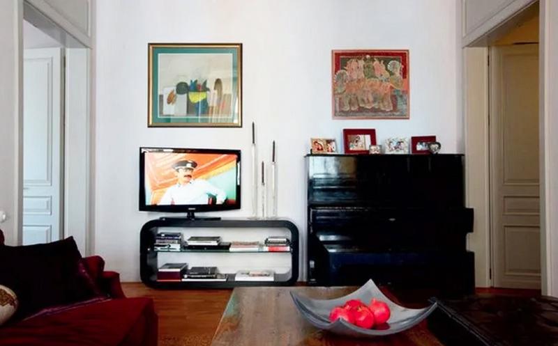 Современная тумба под телевизор обтекаемой формы прекрасно сочетается со старинным пианино